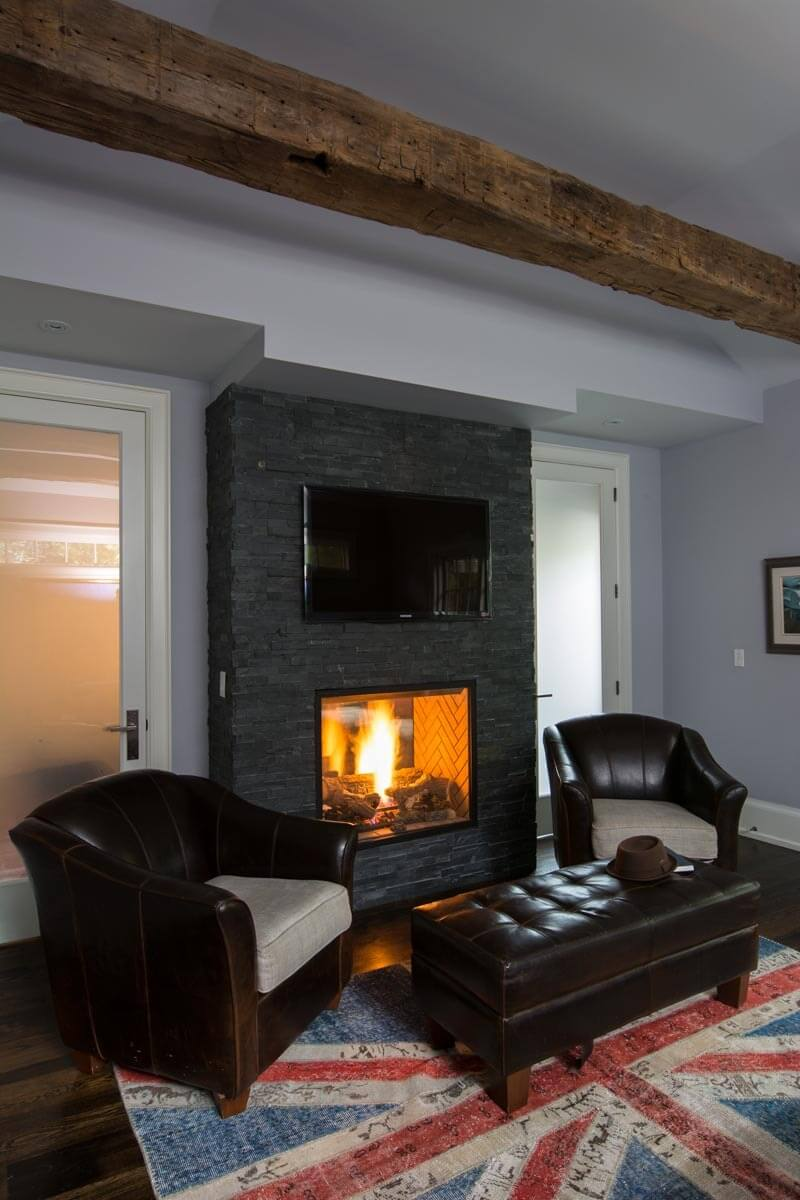 On the other side of the fireplace wall, we see a pair of traditional dark leather armchairs and a matching, oversize ottoman warmed by the fire on a Union Jack styled rug over dark hardwood flooring.