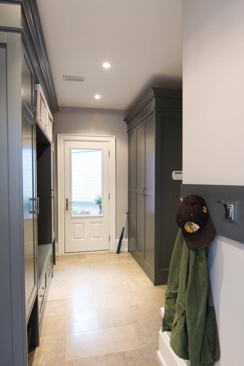Entry way features built-in shelving and cabinetry at left, with matching dark grey toned free standing cabinets across the hall space. This tone adds contrast and detail, setting this space apart from the rest of the home.