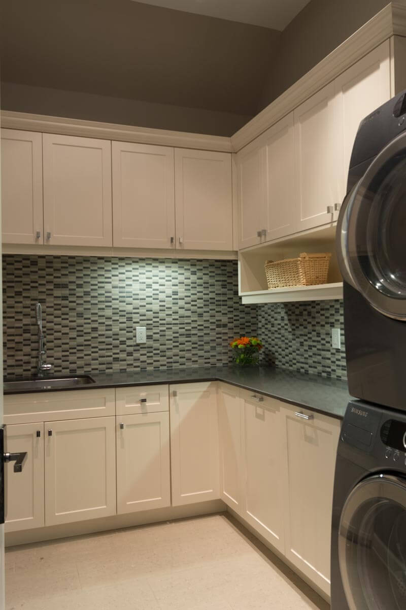 Full fledged laundry room features dark countertops beneath a patterned tile backsplash, with upper and lower cabinets in white.