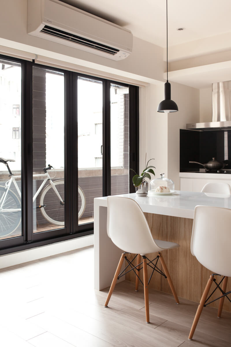 A closer view of the kitchen island, highlighting the simplicity of the chairs and providing a better view of the door to the balcony.