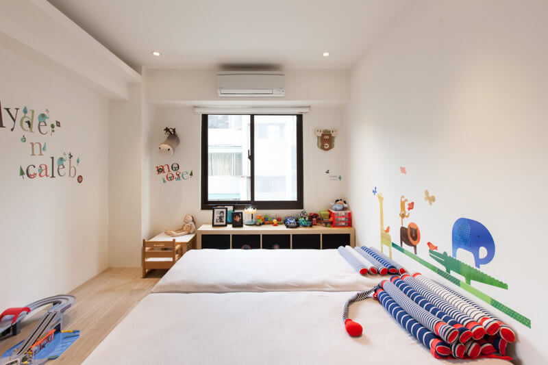 The bright children's room is decorated with primary colors and various vinyl decals. A storage unit for toys is on the far wall under the window.