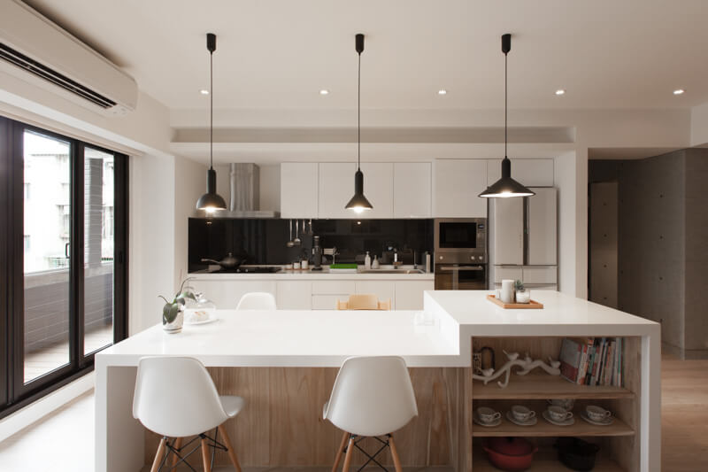 A straight-on view of the kitchen, showing the open storage next to the bar, the stainless steel appliances and the differently shaped pendant lights.