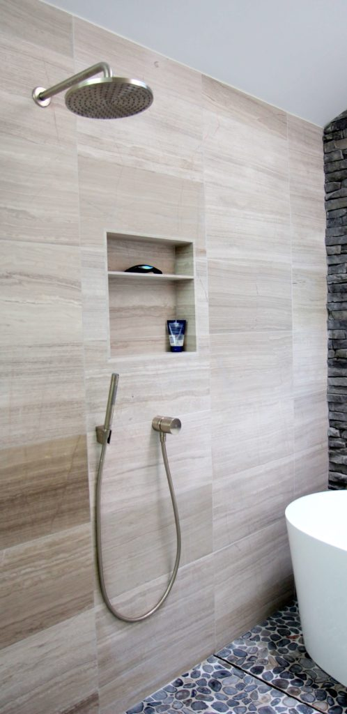 Next to the Victoria and Albert tub extending from the wall is a brushed nickle shower head and hand shower with a digital. The floor houses a hidden drain. A small built-in cubby houses shower products.
