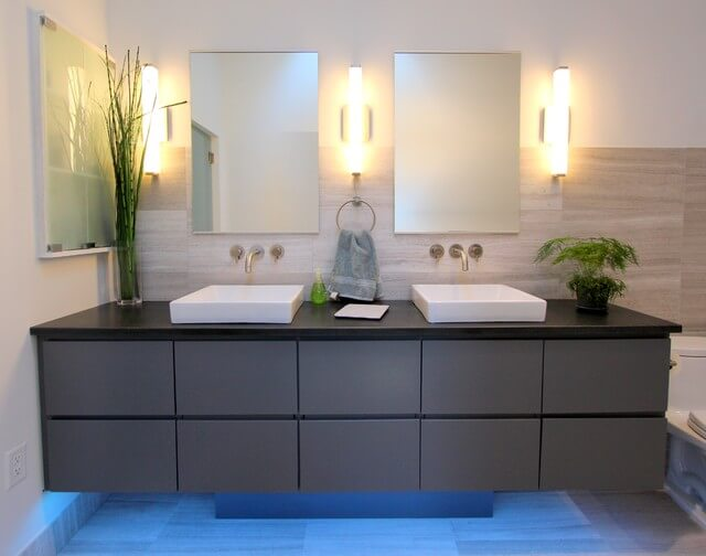 A straight on view of the vanity for the complete effect. LED lights on the bottom, plenty of roomy drawers, two mirrors, a medicine cabinet and green plant accents.