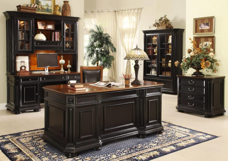 The executive desk is the big king of the home office world. With loads of drawer storage and surface area, along with an often massive footprint, these carved wood specimens impart a sense of grandeur and timeless appeal that stands apart from other styles. Often what is pictured when considering a traditional desks, the executive desk can encompass anything from a single rectangular desk to an entire office suite, as pictured here.