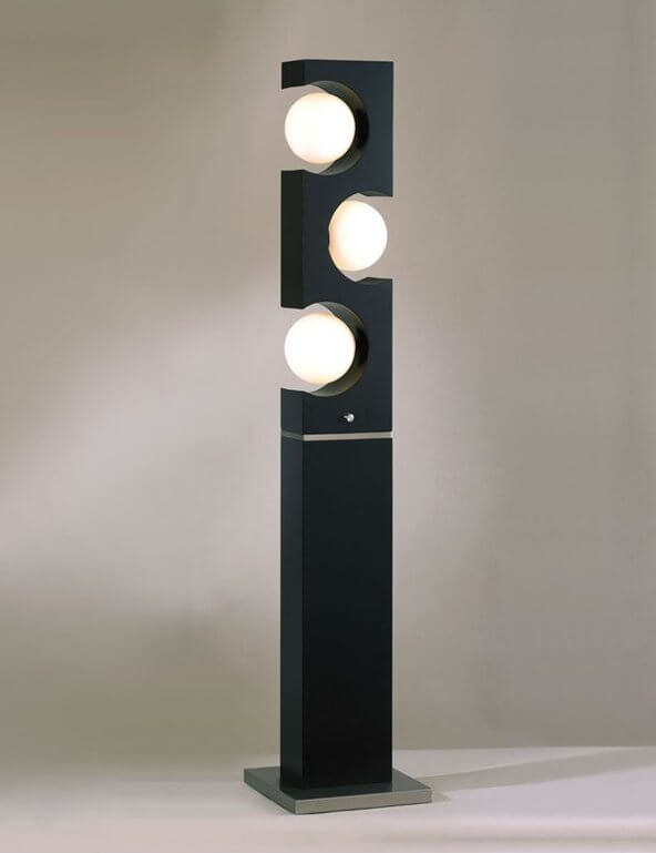 This lamp features a minimalist black slab design, with circular cutouts for 3 light spheres in the top half.