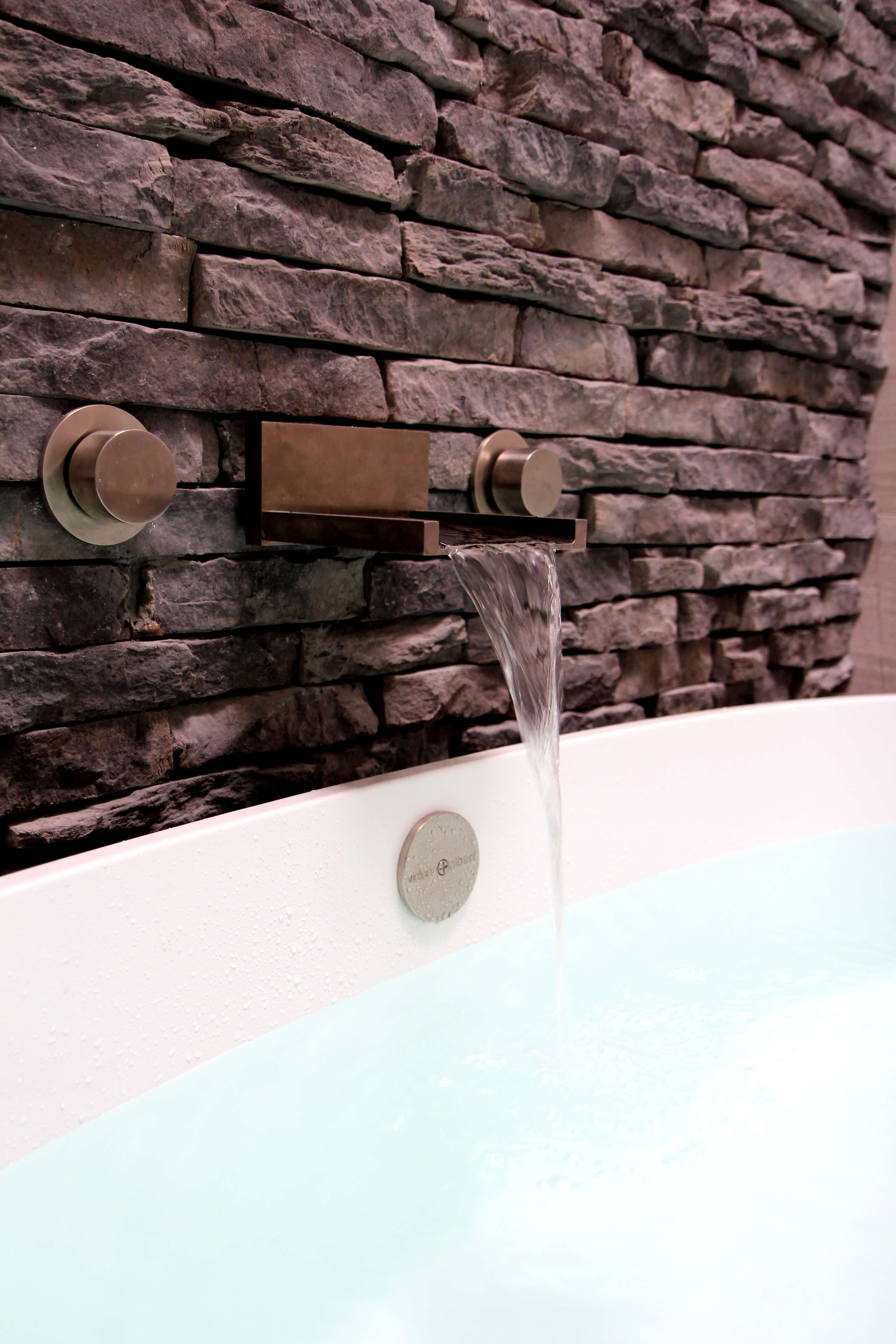The faucet extending from the stacked stone wall is brushed nickle and sleek, provoking the image of a small waterfall.