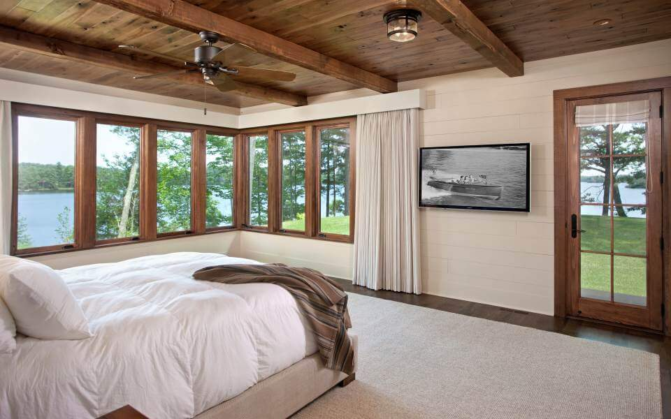 This bedroom, with white bedding on light beige area rug covering the hardwood flooring, features expansive views through wraparound windows. Exposed beam ceiling appears again here.