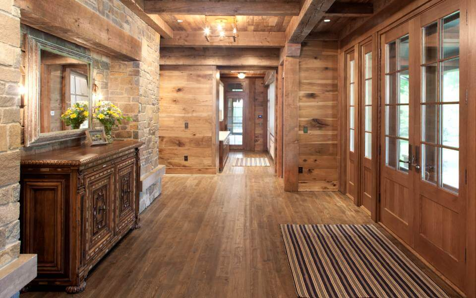 Entry space is flush with more natural wood panels, exposed beams, and stone work reprising the exterior look. Hardwood flooring runs throughout.