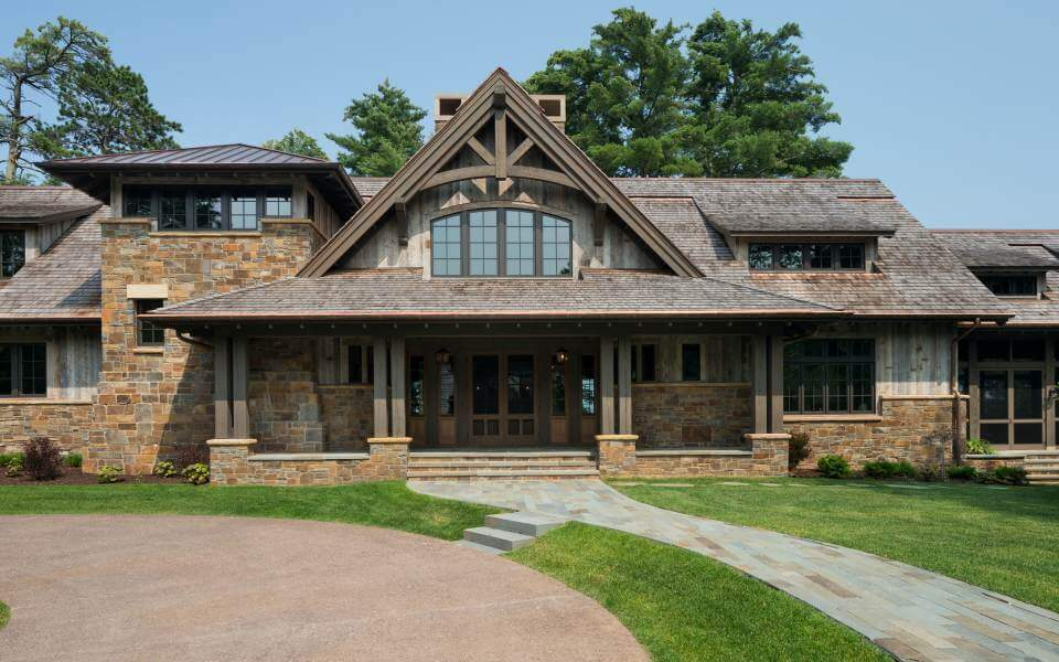 The front porch is fully shaded by a roof overlooked by arched upper floor windows. Four double pillars of natural wood beams wrap the large entryway.