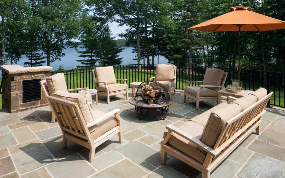 The side patio stands an array of natural wood frame furniture around a standalone fire pit, with views of the surrounding woods and lake.