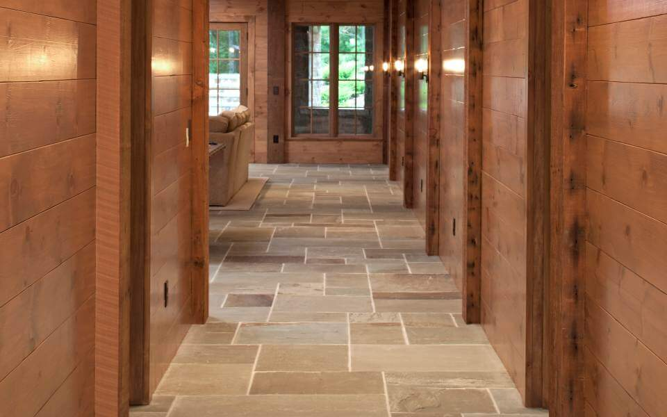 Here we have the main hall running toward the living room, with rich lacquered wood walls interspersed with vertical exposed beams that contrast with the stone tile flooring.