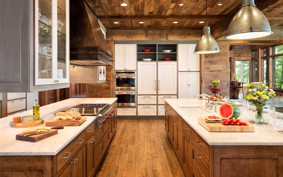 With the kitchen fully lit via recessed lighting in the hardwood ceiling, we see an array of white cabinetry built into the far wall and at left, contrasting with the natural wood surroundings, yet matching the marble countertops.