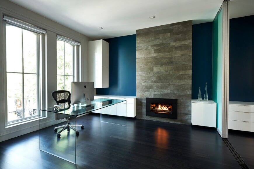 The glass desk adds a delicate touch to the stone fireplace, dark wood floors, and dark blue walls. White trim and cabinets add contrast.