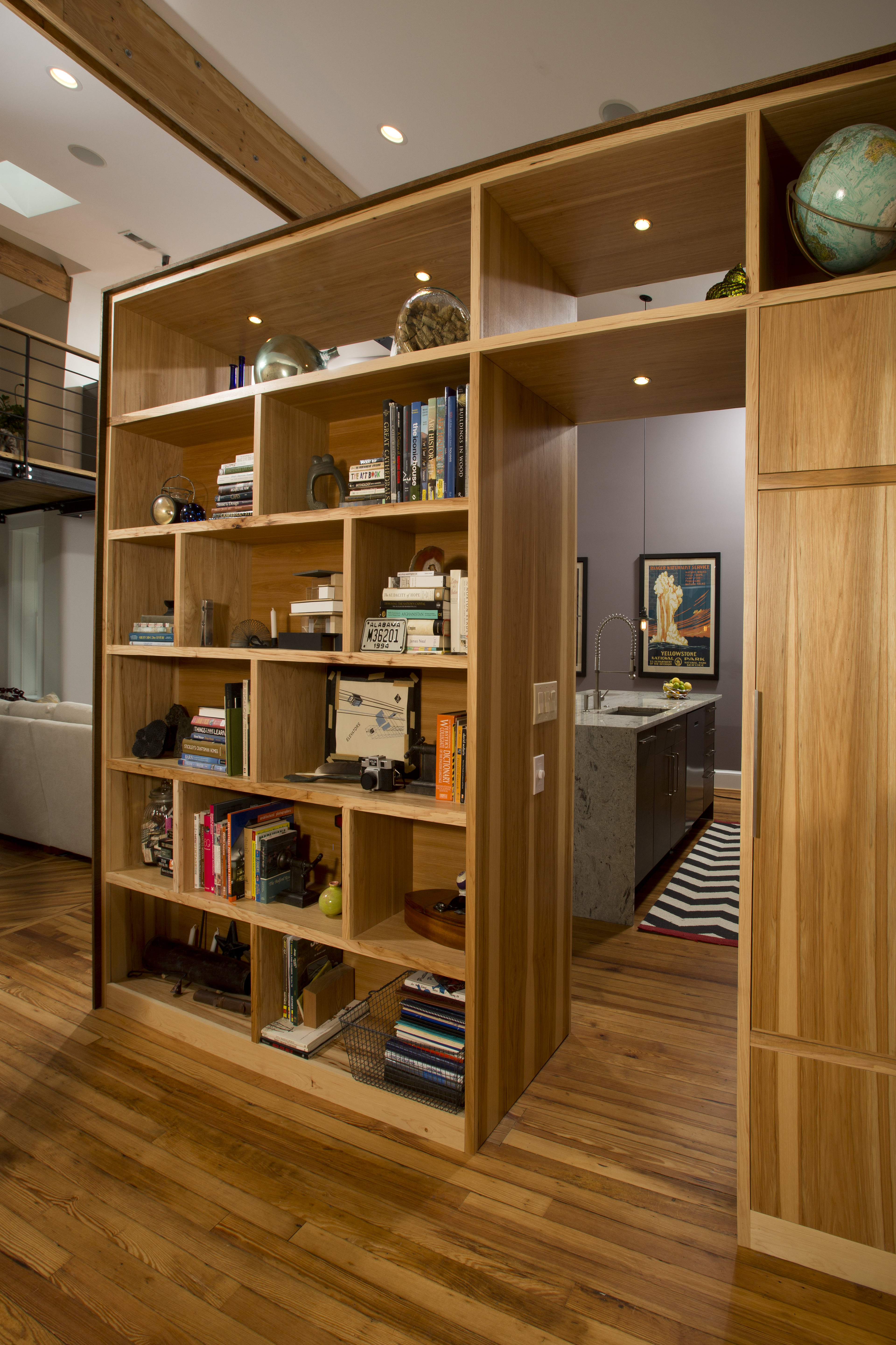 The opposite side of the shelving unit is a large bookcase with many different sized cubbies. The shelving is made out of pine similar to the original flooring.