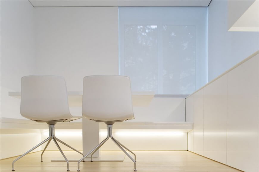 White minimalist design is combined with frosted windows to provide a secluded and bright place to work.