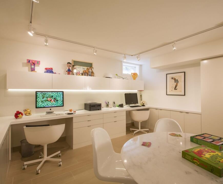 This bright home office has two work stations against the back wall, with under-the-cabinet lighting. A white marble table acts as a play and craft area.