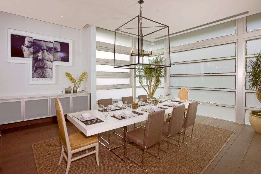 Dining room is surrounded by fogged glass panels for privacy, with a minimalist white slab table and brown chairs over brown area rug at center. Large cubic chandelier hangs overhead, while fractured portrait art piece hangs over cabinetry at left.