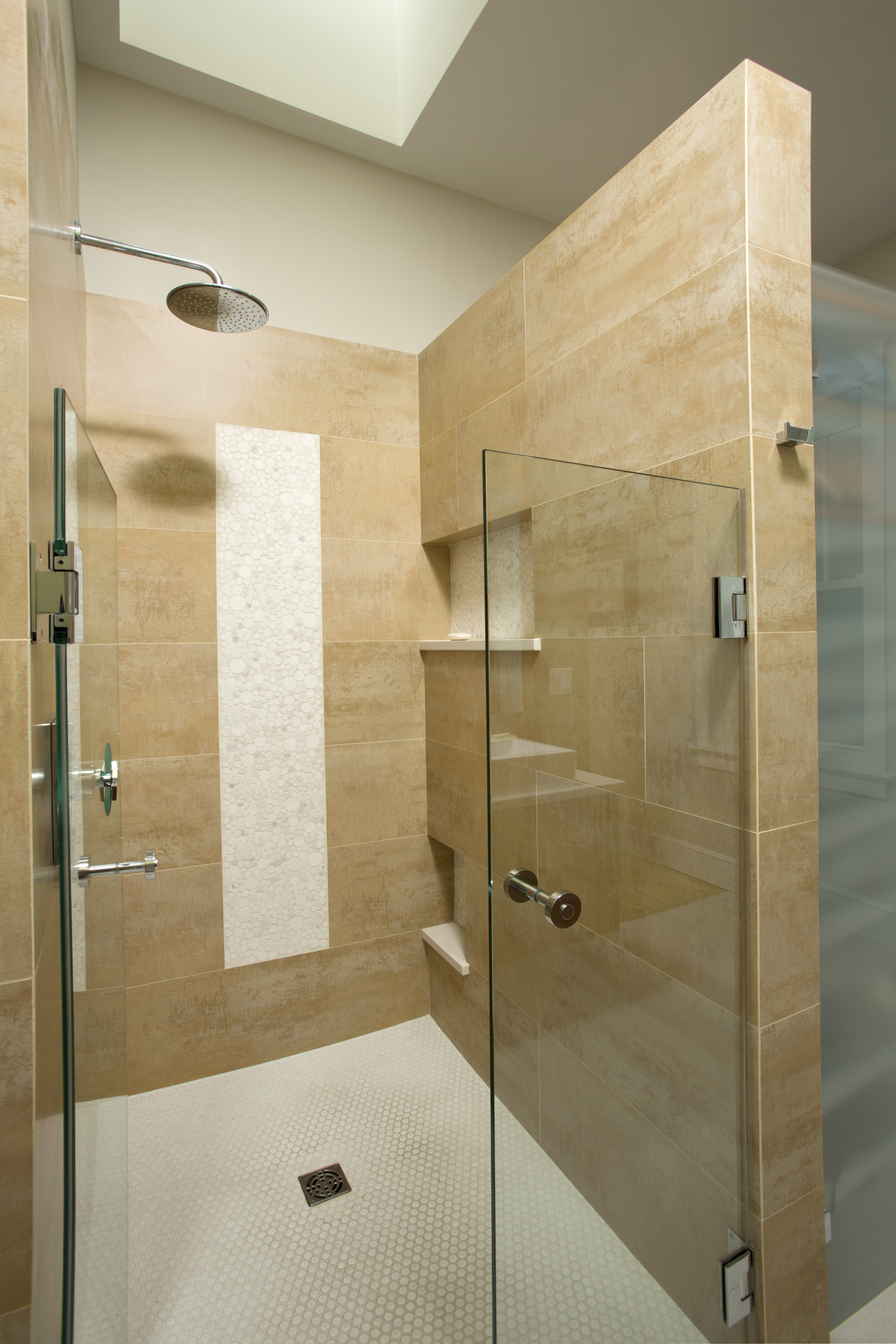 The glass-enclosed shower stall is lined with white tile and natural stone. The roomy stall has built-in cubbies.