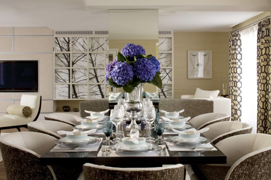 Turning toward the dining area in this large open space, we see a grand dark stained dining table flanked with a set of luxurious barrel chairs with brown outer shells and cream cushioning.