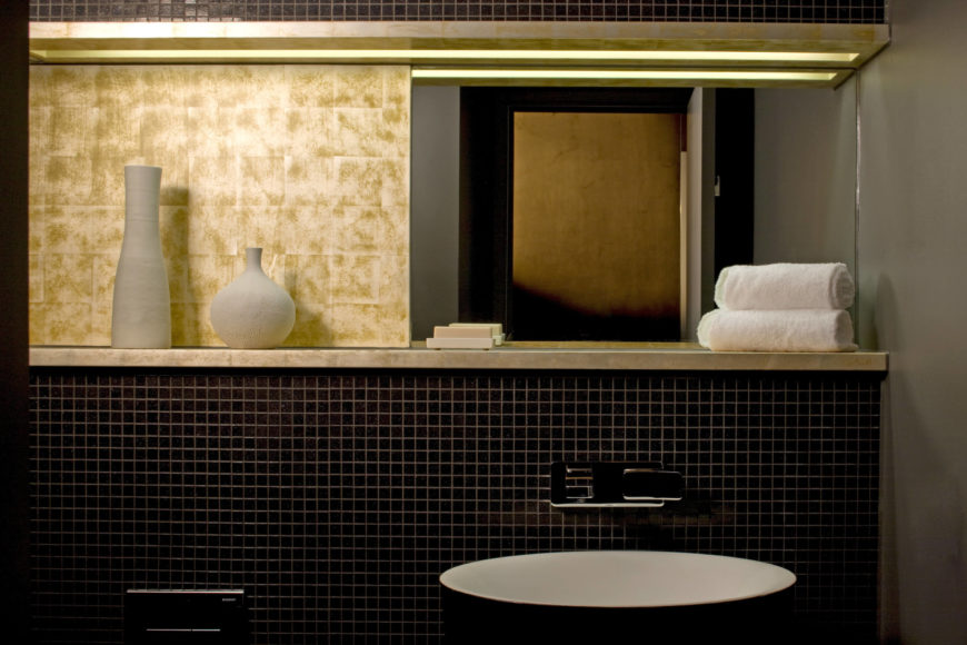In the boldly textured bathroom, we see dark micro tiles and gold marble mixing in a minimalist arrangement. Vessel sink stands below a small shelf and mirror at right.