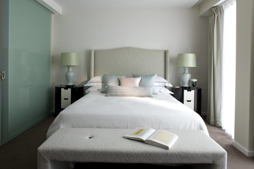 This secondary bedroom features a mixture of the softest tones in the home, including white, sky blue, and light pink. Large ottoman bench sits at the foot of the bed, while a pair of modern dressers in dark wood with white drawers flank the bed.