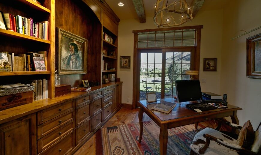 This rustic home office has a large built-in bookcase with drawers beneath. The antique wooden desk is protected by a glass top and positioned diagonally to take advantage of the light from the glass doors to the patio. A cow-hide chair and antler light fixture add rustic charm.