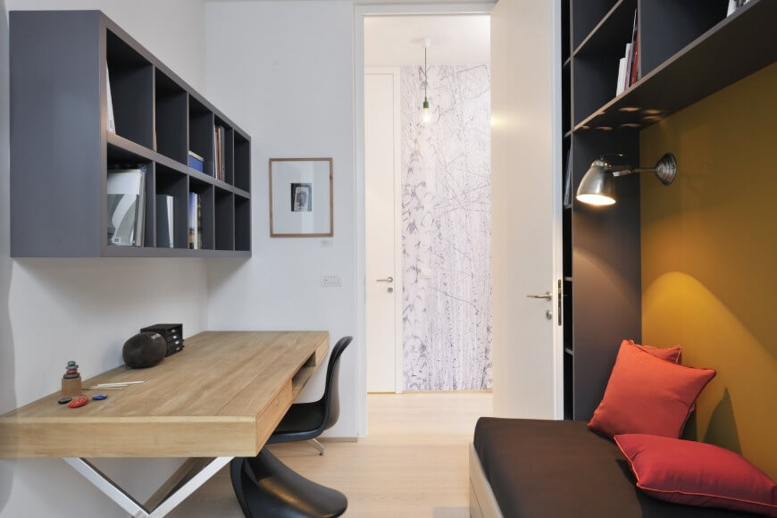 This minimalist home office is on the smaller side, with a simple light wood and metal desk with a curvy chair and a comfy storage bench. Wall storage hangs above the desk for easy reach. Further storage is built around the bench, behind which is a bright accent wall.