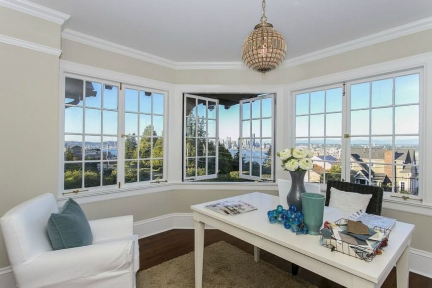 This smaller contemporary home office has white furniture matched with light cream walls and an area rug. An orb light fixture with crystal accents hangs high from the ceiling. The three large windows open out to let fresh air in. The room has a beautiful view of the city and water.