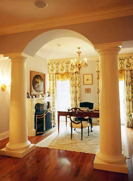 This grand home office is separated from the other room by large columns. The ornate open-hearth fireplace is covered by a gilded screen, and is close enough to keep the occupant of the room toasty warm.