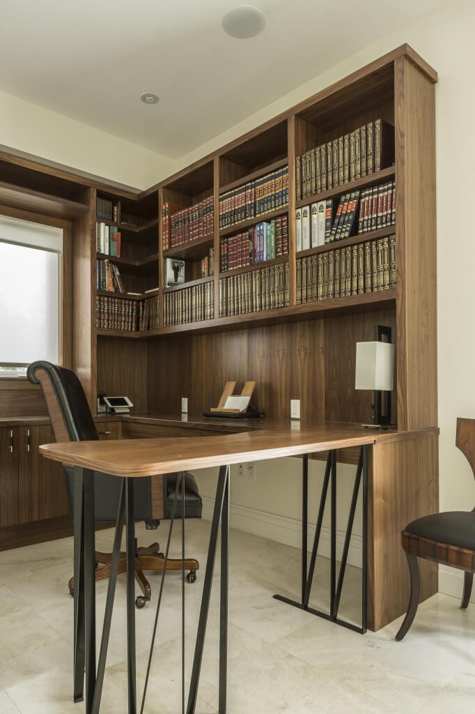 The built-in bookcase and desk extends into the middle of the room and wraps around two walls for plenty of workspace and storage. The light tile floor contrasts with the dark wood and black metal supports of the desk.