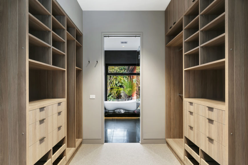 A large walk-in closet leading to the master bath is flanked by floor to ceiling natural wood cabinetry.