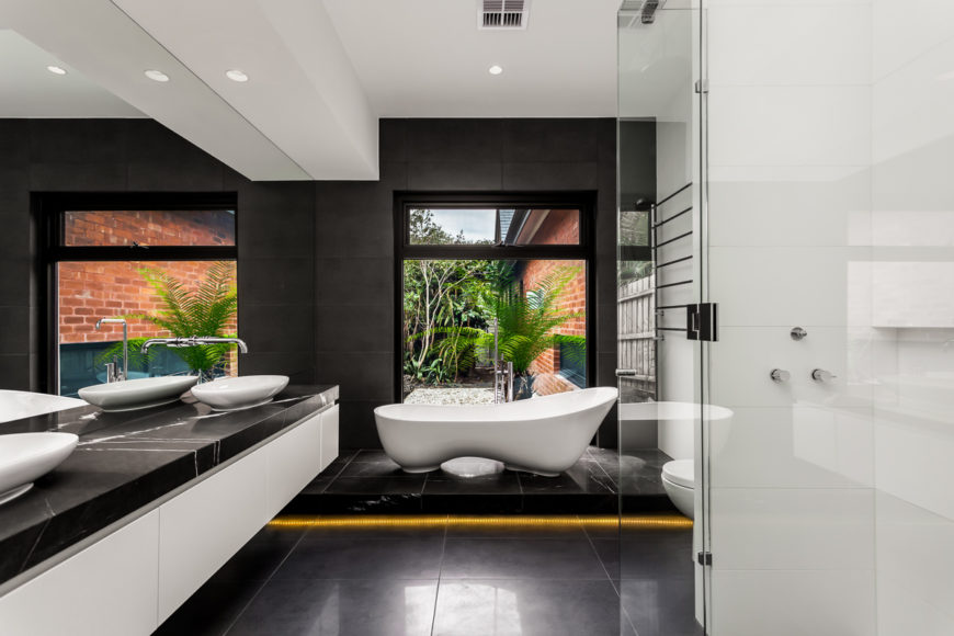 The master bath is a stunning achievement, featuring high contrast between dark marble flooring, countertops, and walls, and the white vanity structure, vessel sinks, and unique oblong pedestal tub. Featuring a glass enclosure shower and large format window overlooking the garden, this is a boldly realized space.