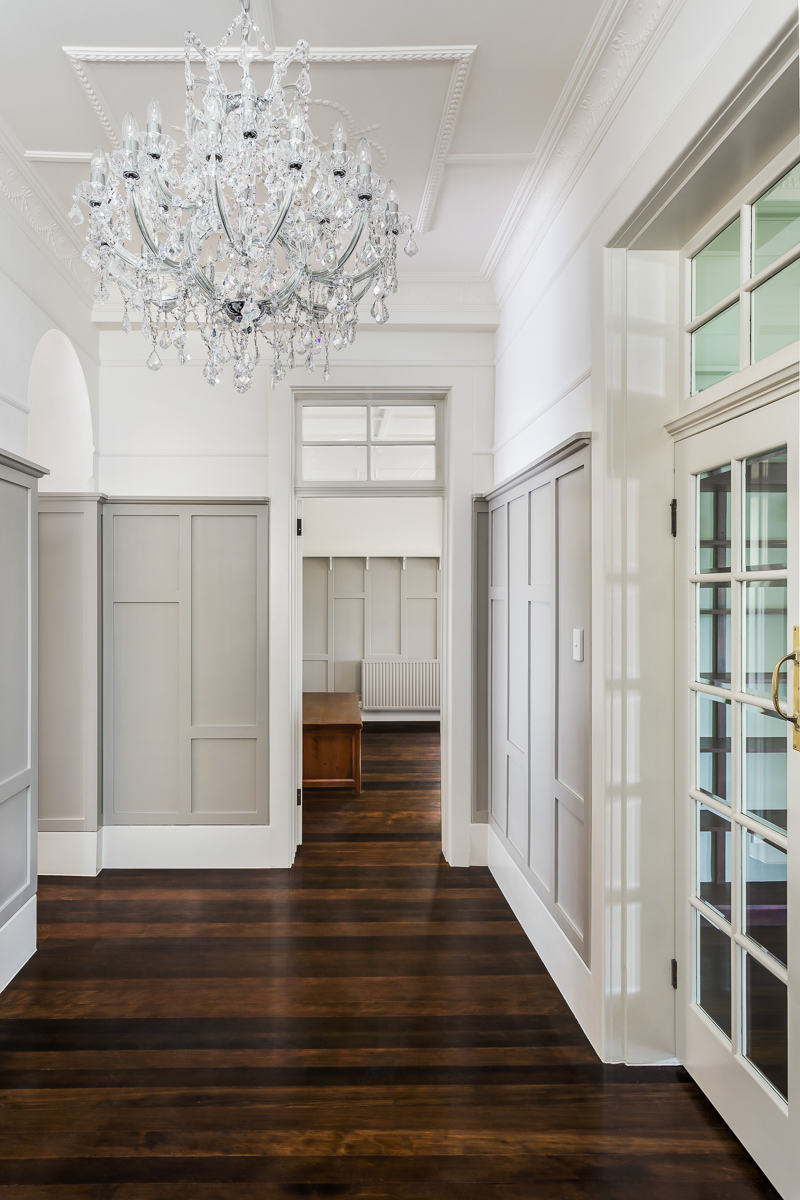Stepping back into the main hall, we see the spectacular chandelier hanging overhead, defining an elegance throughout the space. White walls and glass panel doors contrast with the rich natural tones of the flooring.