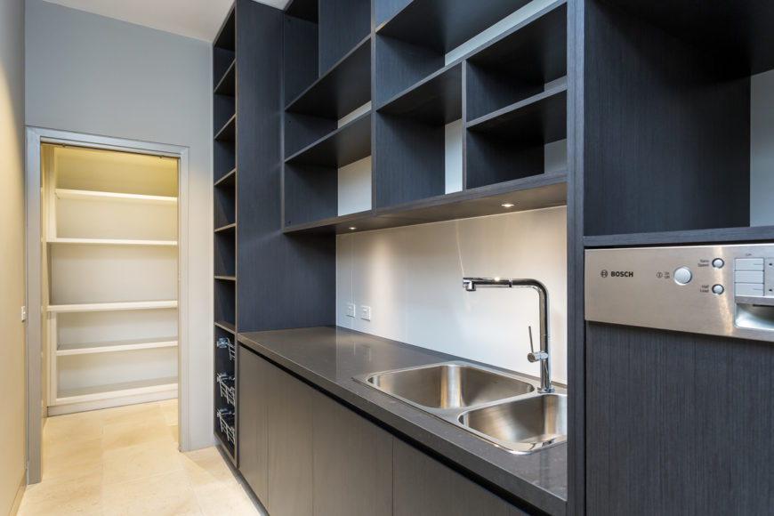Moving away from the kitchen, we see a laundry space decked out with floor to ceiling black wood cabinetry and a stainless steel countertop holding large scale sink. Walk-in storage can be seen at left.