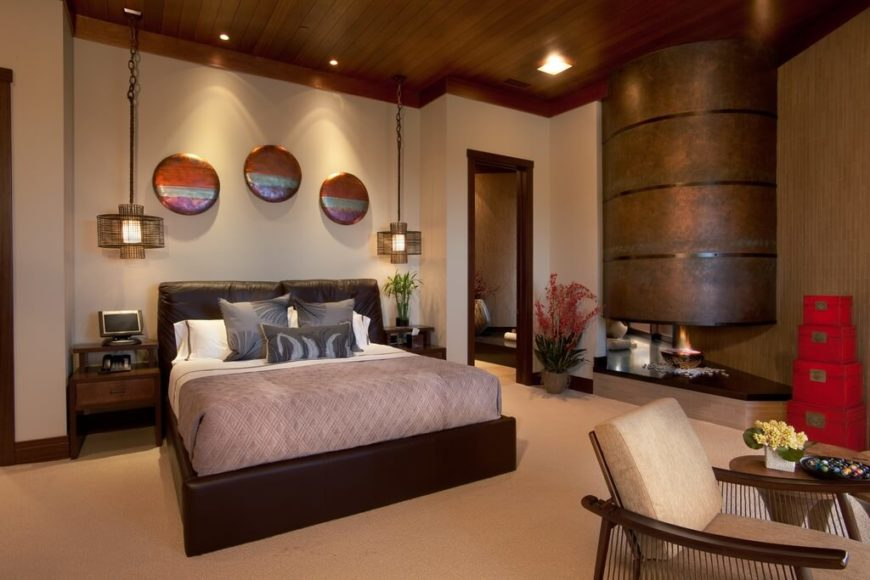 An open, modern fireplace is the focal point of this room, with rich browns and textures including the leather bed frame.