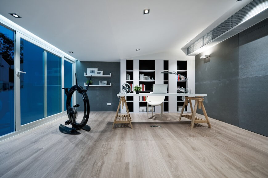 Another example of a modern and minimalist home office with pale natural wood floors and slate-gray walls. The desk is white topped, supported by sawhorses. A built-in bookcase with black backing sits against the far wall.