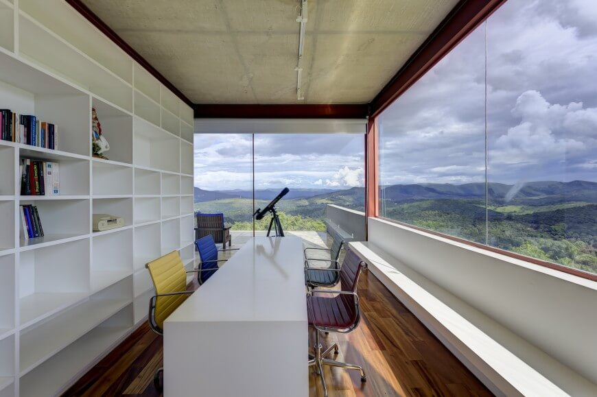 This narrow home office has a huge built-in white bookcase the matches the minimalist table and the bench that runs along the right wall. Floor-to-ceiling windows provide spectacular views of the countryside. Colorful chairs seated at the desk provide a pop of color.