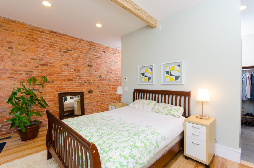 The first bedroom, around the corner from the bathroom and walk-in closet, mixes dark and light wood in the furniture. The original brick wall acts as an accent.