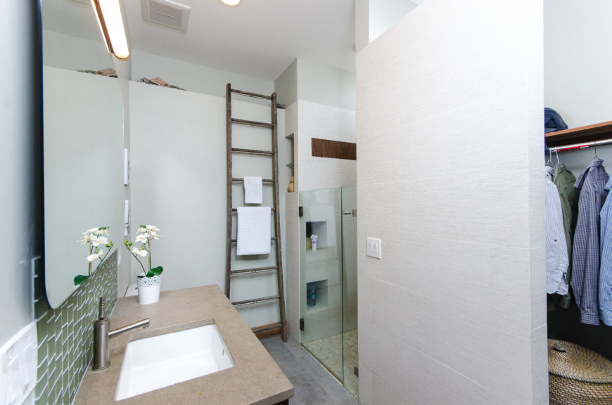 A shorter glass door encloses the white tile shower with built-in cubbies. Around the corner is a walk-in closet.