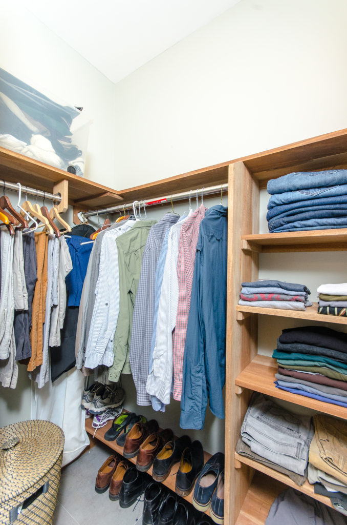 The walk-in closet has plenty of custom shelving for storage, and a wicker basket for laundry.