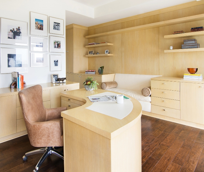 The curve of the desk allows it to be positioned anywhere in the room easily. The built-in cabinets and bench match the desk. The faux leather desk chair pulls warmer shades from the hardwood flooring.
