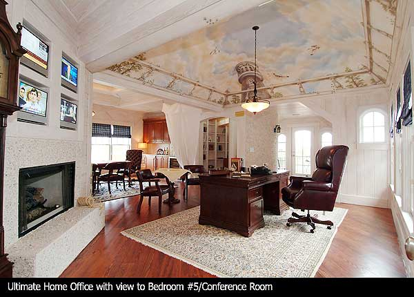 This spacious home office has a gorgeous photo ceiling vaulted upwards. The room also contains a large enclosed fireplace and four television screens above it.