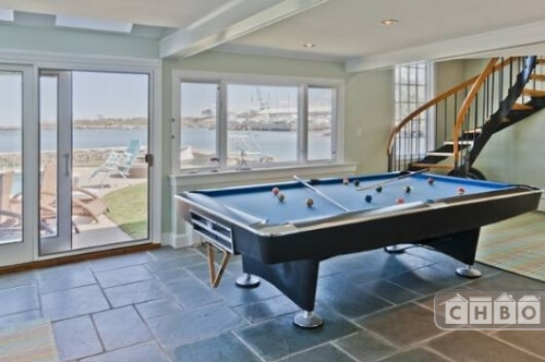 The recreation room on the ground floor has a full-size pool table and natural stone floors. The sliding glass doors lead out to the pool area, which has tons of lounge chairs for sunbathing.