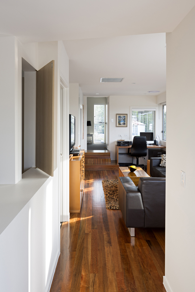 The home office area is tucked neatly into the corner of this living room, beside the small set of stairs to enter the room from the entryway.