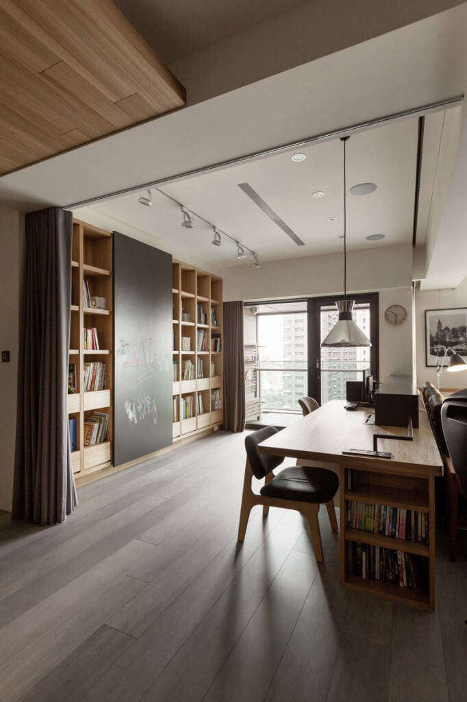 When the curtain is not drawn, the room still feels separate in purpose from the rest of the home. Built-in bookcases in the sides of the desk and along the back wall add a library feel to the room. However, the desk faces the living room, which allows the two spaces to flow together and to interact.