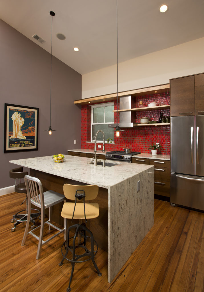 Three mismatched barstools sit at the granite bar of the kitchen island. The chrome fixtures and stainless-steel appliances. The backsplash is a bright, glossy red.