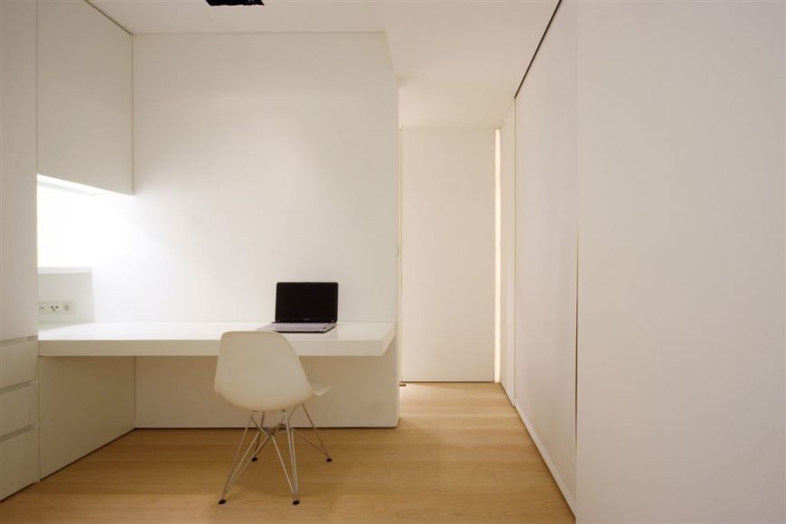 This white minimalist home office has built-in storage hidden in a sleek wall cabinet.