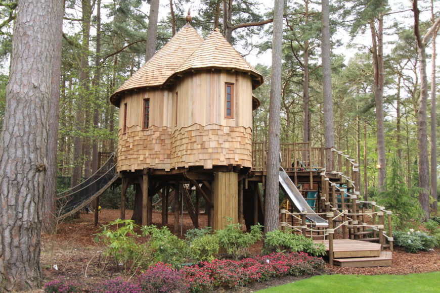 From the left side, a rope bridge leading down the back of the treehouse is seen descending from behind the curved turrets of one of the main treehouses.