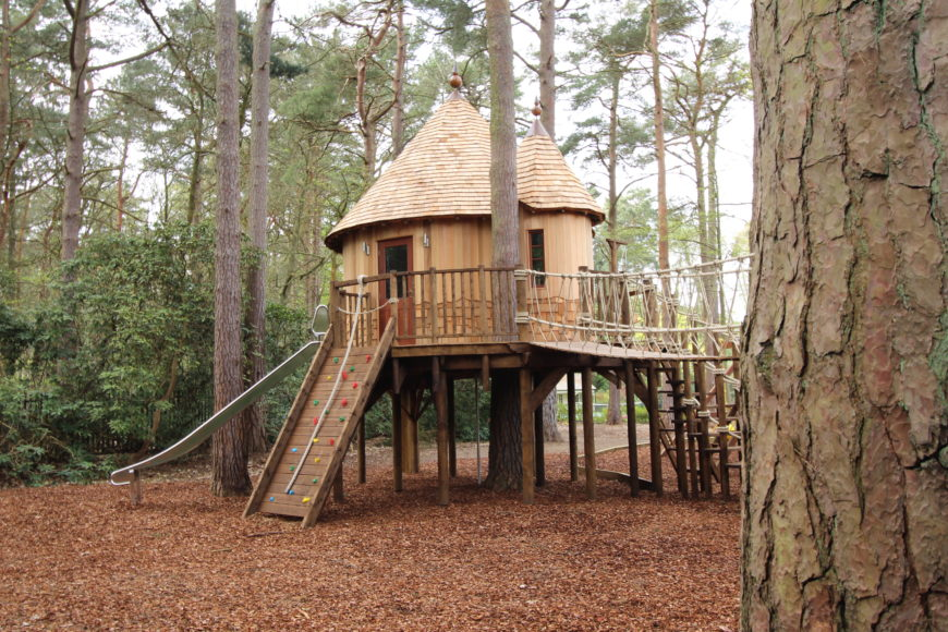 A slide, climbing wall and stairs lead out from the second treehouse. The sturdy connecting rope bridge extends over the soft ground.